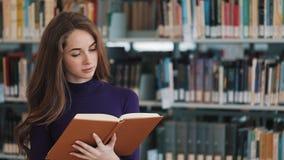 El estudiante joven pensativo lee un libro que se coloca en la biblioteca almacen de metraje de vídeo