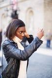 El estudiante joven que caminaba a través de la ciudad paró por un momento para fijar el pelo imagen de archivo