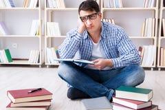 El estudiante joven que estudia con los libros Foto de archivo libre de regalías
