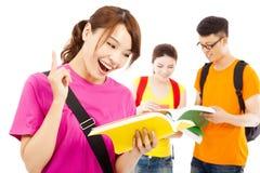 El estudiante joven que lee un libro y piensa hacia fuera ideas Imagen de archivo libre de regalías