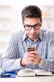 El estudiante joven que manda un SMS mientras que se sienta en sala de clase Fotografía de archivo