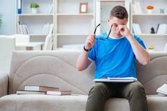 El estudiante joven que se prepara para los exámenes que estudian en casa en un sofá Imágenes de archivo libres de regalías
