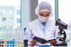 El estudiante joven que trabaja con las soluciones químicas en laboratorio Foto de archivo libre de regalías