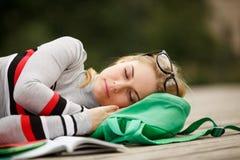 El estudiante joven se cayó dormido con el libro en piso de madera Foto de archivo libre de regalías