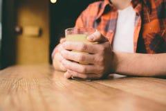 El estudiante joven se está sentando en el restaurante y prueba una bebida caliente té de consumición del hombre en el café Foto de archivo libre de regalías