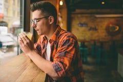 El estudiante joven se está sentando en el restaurante y prueba una bebida caliente té de consumición del hombre en el café Imagenes de archivo