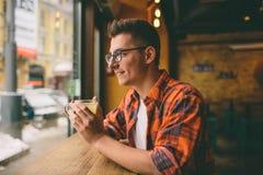 El estudiante joven se está sentando en el restaurante y prueba una bebida caliente té de consumición del hombre en el café Imagen de archivo libre de regalías