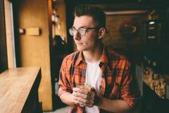 El estudiante joven se está sentando en el restaurante y prueba una bebida caliente té de consumición del hombre en el café Fotografía de archivo libre de regalías
