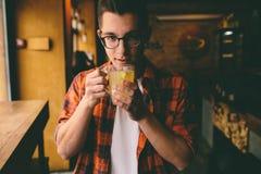 El estudiante joven se está sentando en el restaurante y prueba una bebida caliente té de consumición del hombre en el café Fotos de archivo