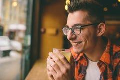 El estudiante joven se está sentando en el restaurante y prueba una bebida caliente té de consumición del hombre en el café Imagen de archivo