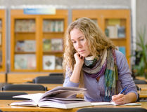 el estudiante lee el libro en biblioteca Fotografía de archivo