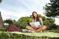 El estudiante lee el libro en el parque y la mirada para arriba Fotos de archivo