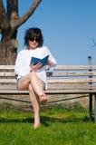 El estudiante lee el libro que se sienta en un banco Fotografía de archivo libre de regalías