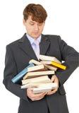El estudiante lleva la pila grande de libros de textos en manos Imagen de archivo libre de regalías