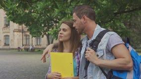 El estudiante masculino abraza a su compañero de clase en campus almacen de video
