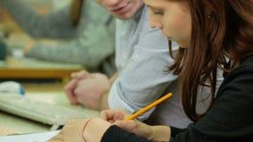 El estudiante masculino aconseja a mujeres cómo anotar correctamente en un cuaderno algo La mujer con el pelo marrón escribe cuid almacen de metraje de vídeo
