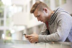 El estudiante masculino adulto joven utiliza smartphone en pasillo de la universidad Imágenes de archivo libres de regalías