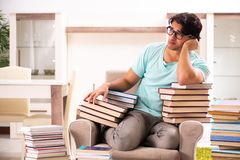 El estudiante masculino con muchos libros en casa imagen de archivo