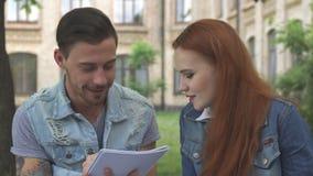 El estudiante masculino escribe algo en su cuaderno almacen de metraje de vídeo