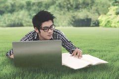 El estudiante masculino está estudiando en el prado Imagen de archivo libre de regalías