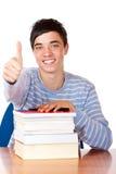 El estudiante masculino feliz con los libros muestra el pulgar para arriba Foto de archivo libre de regalías