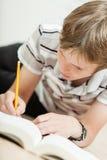 El estudiante masculino joven en el trabajo sobre el suyo estudia difícilmente Fotografía de archivo