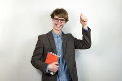 El estudiante masculino joven sonriente hace los pulgares encima del gesto Foto de archivo