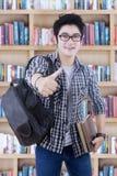 El estudiante masculino muestra los pulgares para arriba en la biblioteca Fotos de archivo