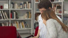 El estudiante masculino muestra a su compañero de clase femenino algo en el ordenador portátil en la biblioteca almacen de video