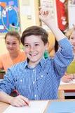 El estudiante masculino Raising Hand To contesta a la pregunta sobre clase Imagen de archivo libre de regalías