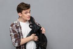 El estudiante masculino saca algo de la mochila Foto de archivo libre de regalías