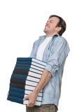 El estudiante masculino sostiene la pila pesada de libros fotos de archivo