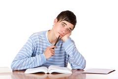 El estudiante masculino triste joven aprende con los libros de estudio Imagen de archivo libre de regalías