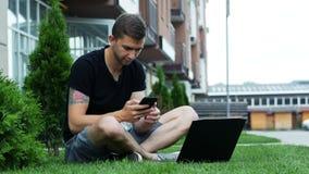 El estudiante masculino utiliza el teléfono y el ordenador portátil mientras que se sienta en hierba almacen de video