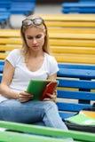 El estudiante mira la tableta que se sienta en banco Imágenes de archivo libres de regalías