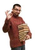 El estudiante moderno con los vidrios satisfecho guarda la pila de libros Imagen de archivo libre de regalías