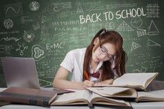 El estudiante moreno aprende en la tabla en clase Imagen de archivo