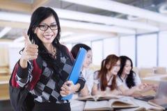 El estudiante muestra el pulgar para arriba mientras que sus amigos aprendizaje Fotografía de archivo libre de regalías