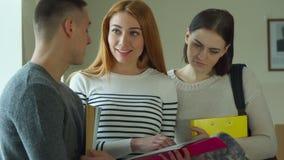 El estudiante muestra su libro de ejercicio a su compañero de clase masculino almacen de metraje de vídeo
