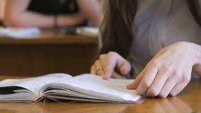 El estudiante mueve de un tirón las páginas del libro de escuela almacen de video