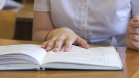 El estudiante mueve de un tirón las páginas del libro de escuela almacen de metraje de vídeo