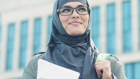 El estudiante musulmán feliz que sostiene los libros, disfruta en la oportunidad del aprendizaje almacen de video