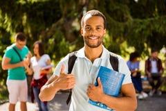 El estudiante nerdy africano acertado alegre joven está mostrando el pulgar imágenes de archivo libres de regalías