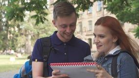 El estudiante pregunta a su compañero de clase acerca algo en cuaderno en campus metrajes