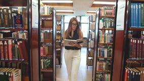 El estudiante que camina a través de la biblioteca y lee la enciclopedia almacen de metraje de vídeo