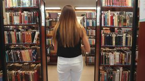 El estudiante que camina a través de la biblioteca y lee la enciclopedia metrajes