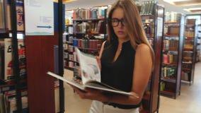 El estudiante que camina a través de la biblioteca y lee la enciclopedia almacen de video