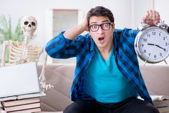 El estudiante que estudia con el esqueleto que se prepara para los exámenes Imágenes de archivo libres de regalías