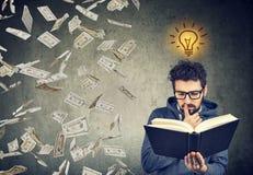 El estudiante que lee un libro tiene una idea brillante cómo ganar el dinero imágenes de archivo libres de regalías
