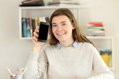 El estudiante que muestra un teléfono elegante en blanco defiende en casa Fotografía de archivo libre de regalías
